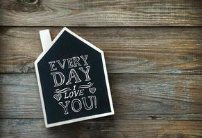 husformade svarta tavlan på rustikt trä välkomnande hem foto