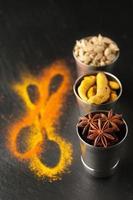 kryddor på svarta tavlan: kardemumma, gurkmeja och kardemumma foto