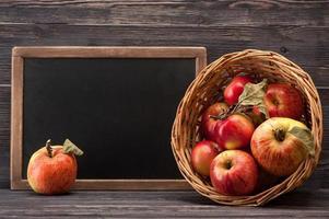 röda äpplen i korg med plats för text på svarta tavlan foto