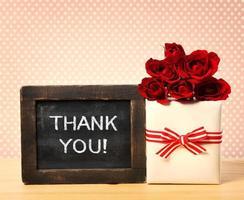 tackmeddelande på svarta tavlan med rosor och presentask foto