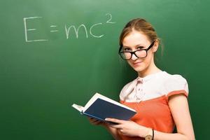 student som står vid svarta tavlan med e = mc2 foto