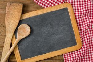 svarta tavlan med träskedar på en röd rutig bordduk foto