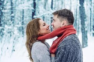 porträtt av lyckliga par i vinter park foto