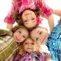 söta glada barn som tittar ner och håller händerna foto