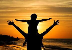 far och son som har kul vid solnedgången
