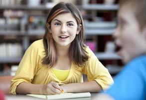 tonårsflicka studerar med pojke foto