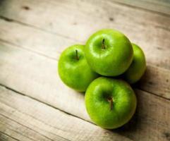 frukt. gröna äpplen på träbakgrund foto