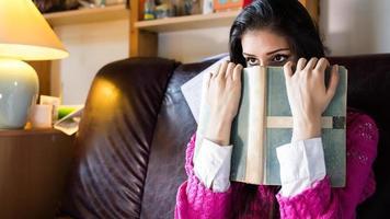 rolig brunettkvinnastudent som försöker studera foto