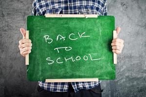 man håller svarta tavlan, tillbaka till skolan foto