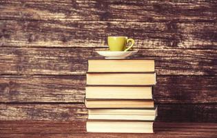 böcker och kopp kaffe på träbakgrund. foto