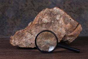 sten och förstoringsglas på träbord. foto