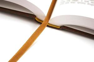 öppnad bok med gyllene bokmärke foto