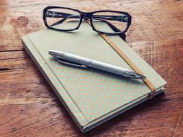 böcker och glasögon på träflisen foto