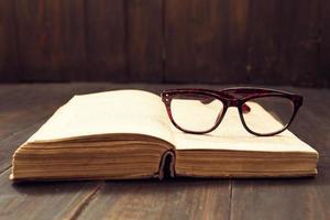vintage läsglasögon på den öppna boken foto