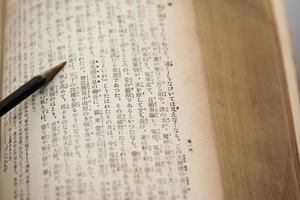 missfärgad gammal japansk bok och penna foto