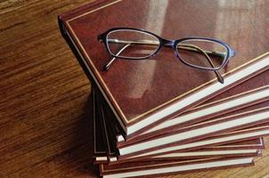 bunt med böcker och glasögon ovanifrån foto