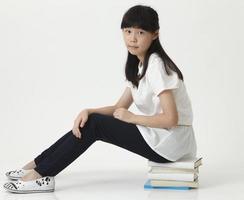 flicka sitter på böcker foto