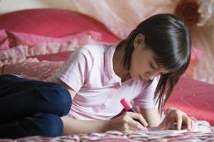 tjej gör läxor i sängen foto
