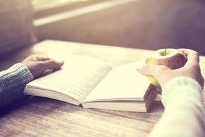 flicka med äpplet och en bok