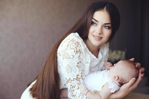 mamma med mörkt hår poserar med sitt lilla bedårande barn foto