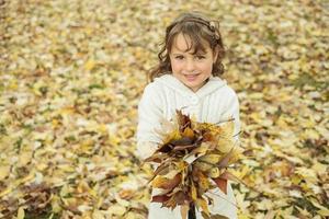 liten flicka med höstlöv foto
