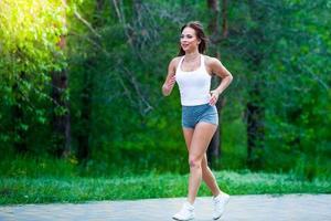 ung kvinna som joggar i parkens sommar foto
