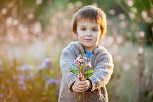 söt liten pojke som håller blommor vid solnedgången foto