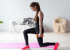 atletisk kvinna som värmer upp och gör viktade lunges med hantlarträning foto