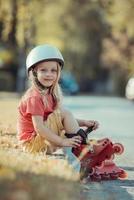 liten flicka som bär rullskridskor