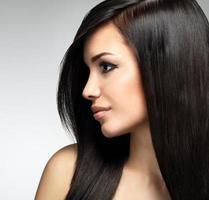 vacker kvinna med långa bruna hårstrån foto