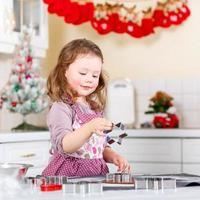 liten flicka som bakar pepparkakakakor i inhemskt kök foto