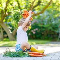 förtjusande litet barn med morötter i inhemsk trädgård foto