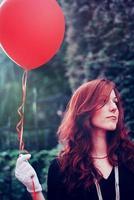 flicka med en röd ballong foto
