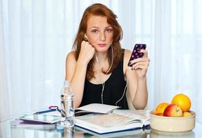 attraktiv tjej med fräknar studerar hemma foto