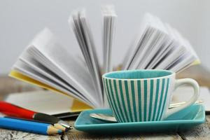 kopp kaffe med öppen bok i bakgrunden foto