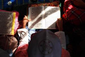 närbild muslimskt barn och bok foto