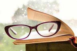 glasögon och boken över fönstret foto