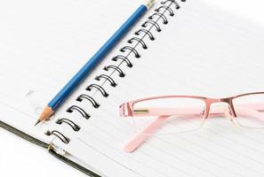 glasögon och penna plats på boken. foto