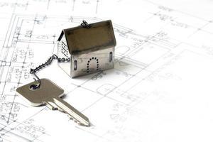 litet hus modell med en husnyckel på arkitektonisk ritning foto