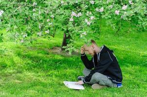 ung man läser en bok under blommande träd foto