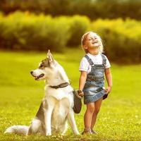 liten flicka med en skrovlig hund foto