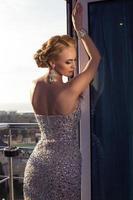 vacker elegant kvinna med blont hår i lyxklänning foto