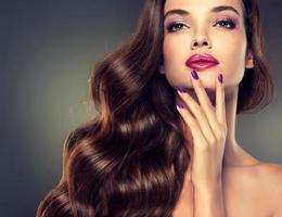 vacker modell brunett med långt lockigt hår. foto