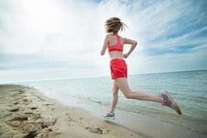 ung dam springer på den soliga sommarsandstranden. träna foto