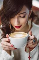 ung flicka som dricker kaffe i ett trendigt kafé foto