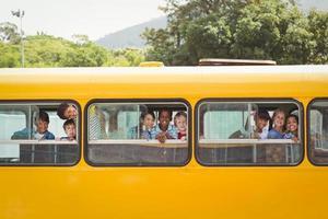 söta elever som ler mot kameran i skolbussen