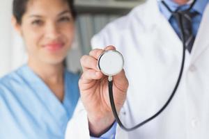midsektion av läkare som håller stetoskop foto