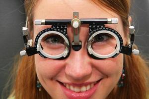 ung flicka på optiker som kontrollerar sin vision foto