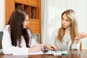 läkare som föreskriver medicinering till kvinnan foto