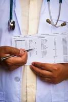 läkare med ett stetoskop som visar onormalt laboratorieresultat foto